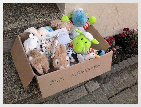 Karton mit vielen Plüschtieren auf einer Treppenstufe an einem Hauseingang. Auf dem Karton steht »Zum Mitnehmen« geschrieben. Gesehen in der Albertstraße in Hannover-Linden.
