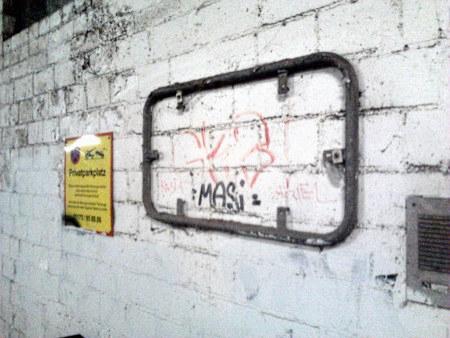 Ein dreckiger, verrosteter Rahmen für die Anbringung eines Schildes an einer von Schmutz und Zerfall geprägten Mauer im Sockelgeschoss der Ruine des Ihmezentrums in Hannover-Linden