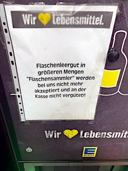Hinweiszettel neben einer Flaschenannahme in einem Edeka-Markt: Wir 💛️ Lebensmittel. -- Flaschenleergut in größeren Mengen -- 'Flaschensammler' werden bei uns nicht mehr akzeptiert und an der Kasse nicht vergütet!!