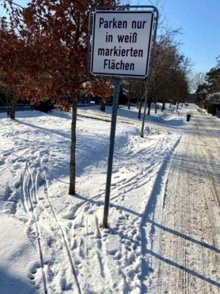 Verschneite Landschaft, darin ein Verkehrsschild: Parken nur auf weiß markierten Flächen