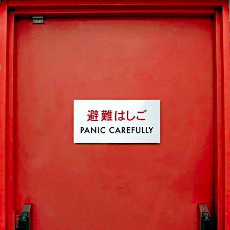 Rote Tür, an der ein Schild mit japanischem Text und englischer Übersetzung angebracht wurde. Die Übersetzung lautet: Panic Carefully