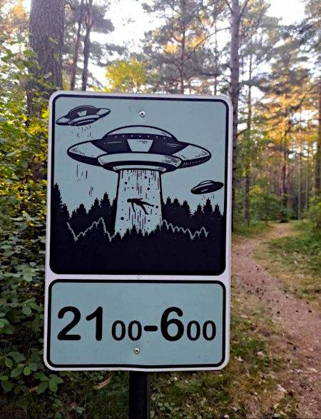 Absurdes Schild, das im Wald aufgestellt wurde. Es zeigt ein UFO, das einen Menschen aus dem Wald mit einem Traktorstrahl hochzieht. Darunter der Hinweis: 21 bis 6 Uhr
