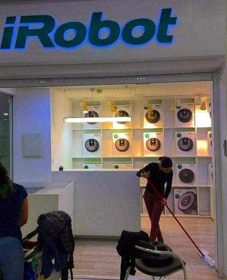 Foto einer Putzfrau in einem mit 'iRobot'-Leuchtreklame beworbenen Verkaufsbereich für Staubsaugerroboter