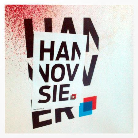 Das Hannover-Logo auf einem Plakat, darüber klebt ein Aufkleber mit der Schreibweise Hannovsie.