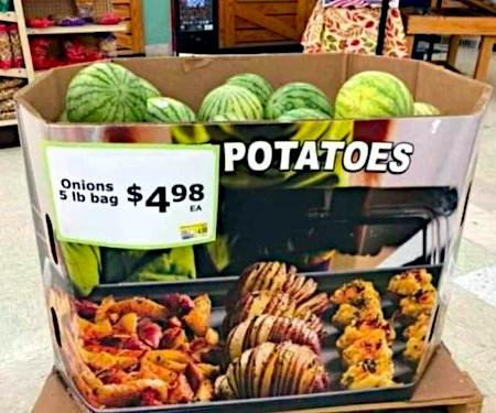 Unbeschreibliches Foto eines Kartons, der mit einem Blech voller Gebäck bedruckt ist, darüber steht 'Kartoffeln'. An dem Karton ist ein Preisschild: 'Zwiebeln, Fünf-Pfund-Tüte $ 4,98. In dem Karton befinden sich Wassermelonen