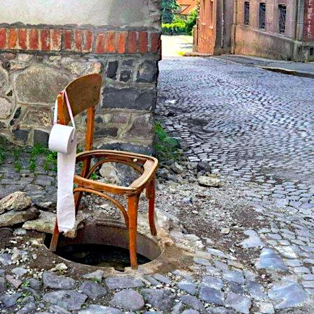 Über einem aufgedeckten Gulli ist ein kaputter Stuhl ohne Sitzfläche gestellt, an der Seite ist mit einem Band eine Rolle Klopapier befestigt.